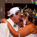 Wedding Couple enjoy first dance at reception while family blows bubbles