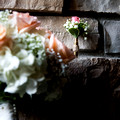 A crafty grooms boutineer in a bullet case with twine and wedding bouquet sitting on bricks