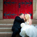 Bride and Groom kissing infront of a bright red door in Piqua Oh